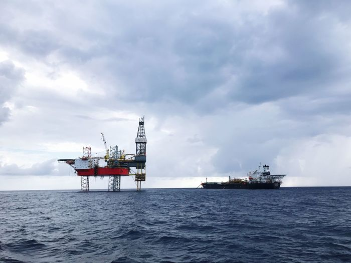 Ship by oil rig in sea against sky