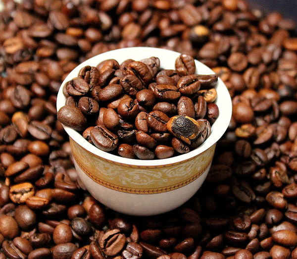 High angle view of roasted coffee beans and cup