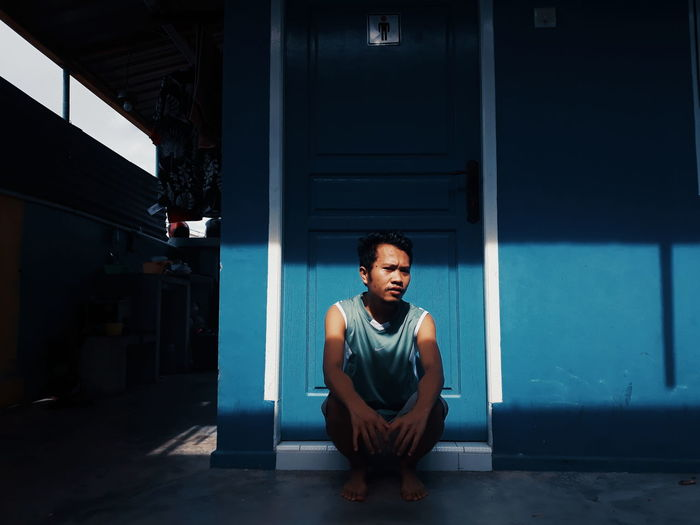 Portrait of a young man sitting in corridor