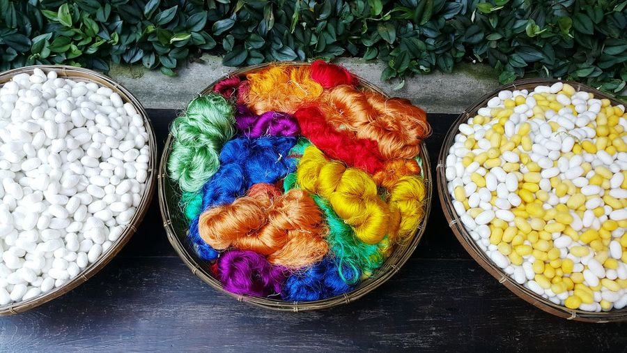 High angle view silkworms and thread in baskets
