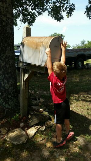 Rear View Of Boy Standing By Mailbox