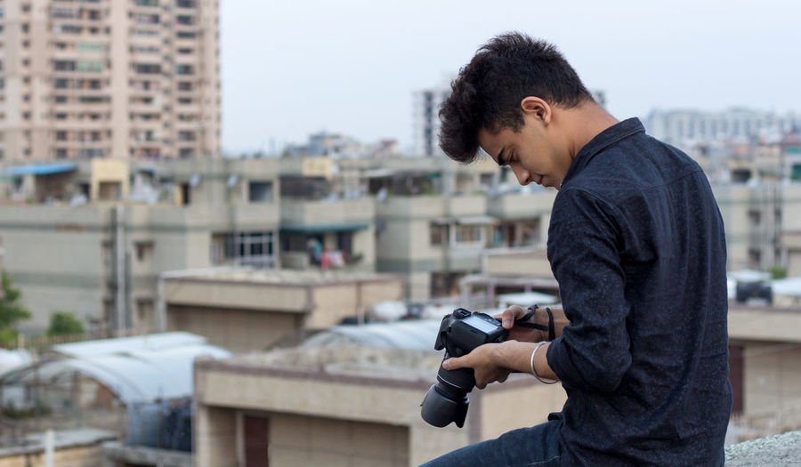 Young photographer exploring terrace while clicking photographs in his dslr camera. world pandemic.