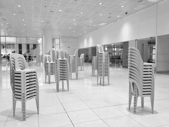 White plastic chairs are stacked up in a white hall in Pasig, Metro Manila. White on white. Indoors  No People Architecture Modern Day White Color White Chairs White Room White On White Philippines Manila Black And White Blackandwhite