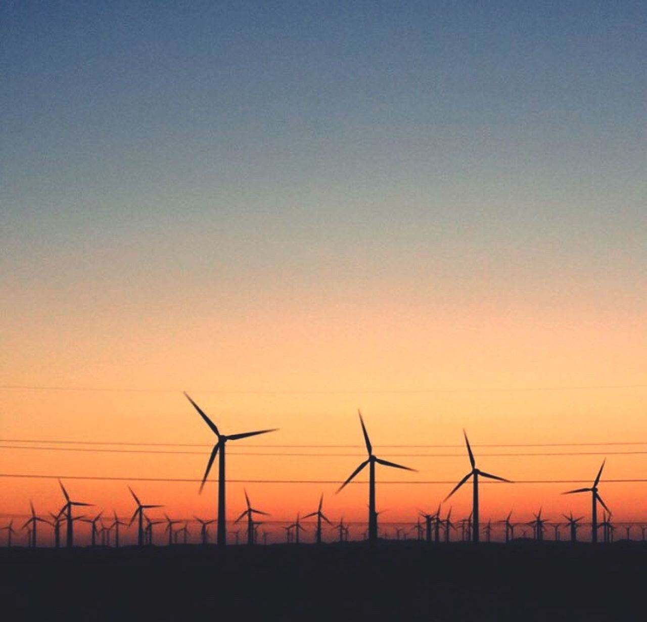 sunset, fuel and power generation, environmental conservation, alternative energy, wind turbine, wind power, no people, orange color, silhouette, nature, renewable energy, sky, copy space, outdoors, scenics, technology, landscape, field, tranquil scene, sun, clear sky, tranquility, windmill, rural scene, beauty in nature, industrial windmill, day