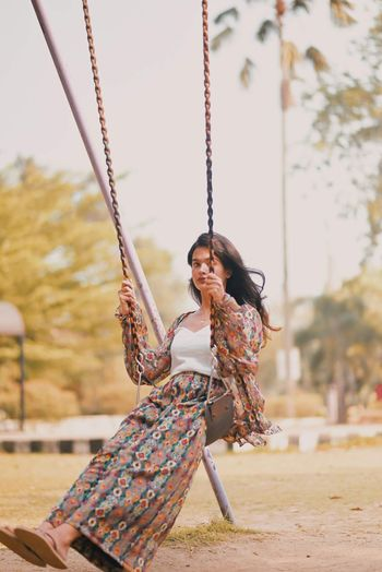 Side view of young woman sitting on swing at playground
