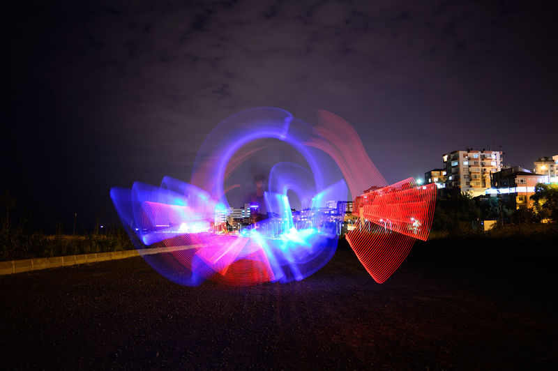Digital composite image of illuminated light trails in city at night