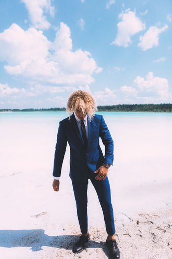Blond curly man dressed in business suit is posing on the crystal clear lake. Trendy hairstyle, awesome shoot. Summer time. Beach Beauty In Nature Casual Clothing Cloud - Sky Curly Hair Day Full Length Hairstyle Land Leisure Activity Lifestyles Nature One Person Outdoors Real People Sea Sky Standing Water