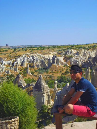 Man looking away while sitting on rocks at nevsehir against clear blue sky