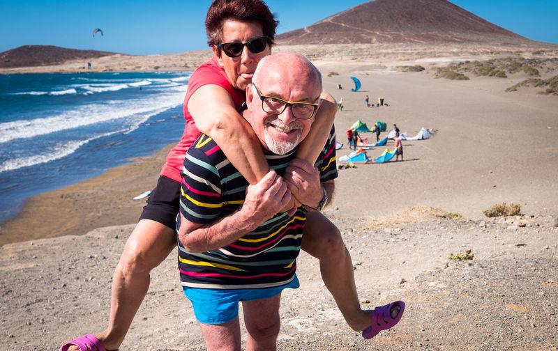 Portrait of smiling man piggybacking woman at beach