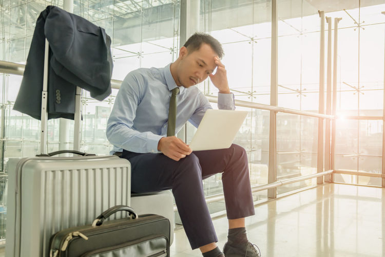 Businessman using laptop while sitting by window in airport