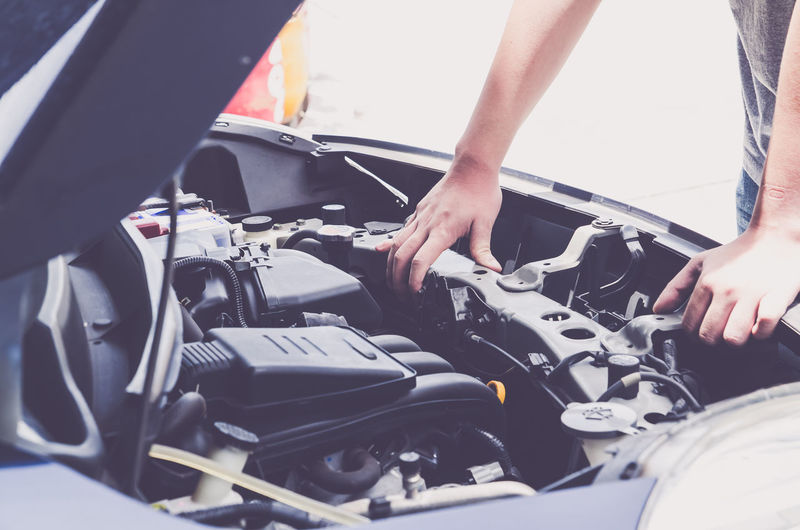 Cropped image of person repairing car