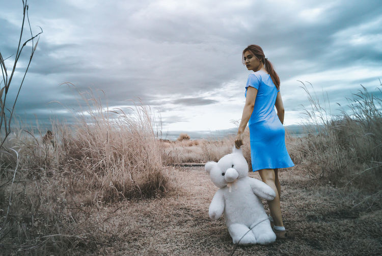 Full length of woman standing with teddy bear on field against cloudy sky
