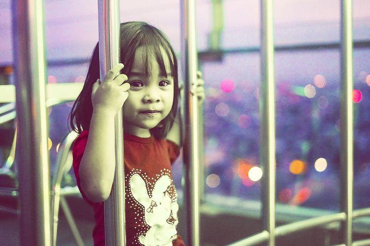 Portrait of cute girl looking through railing