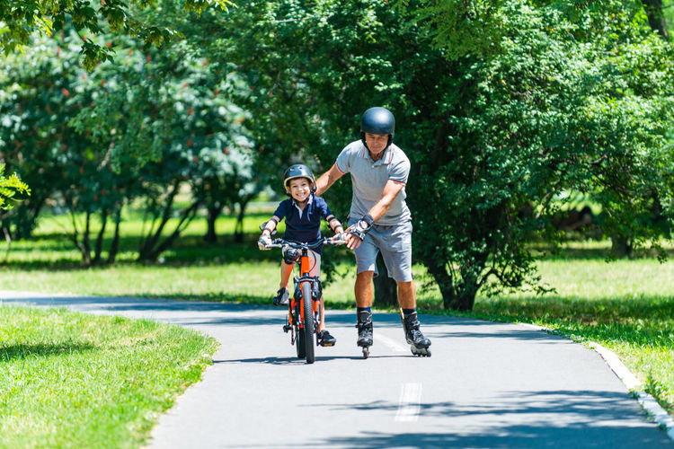 Active Senior With His Grandson Lifestyle Cycle Cyclist Fun Grandfather Grandson Happy Young Bicycle Bike Boy Child Childhood Healthy Helmet Kid Leisure Activity Old Outside Park person Play Ride Senior Summer