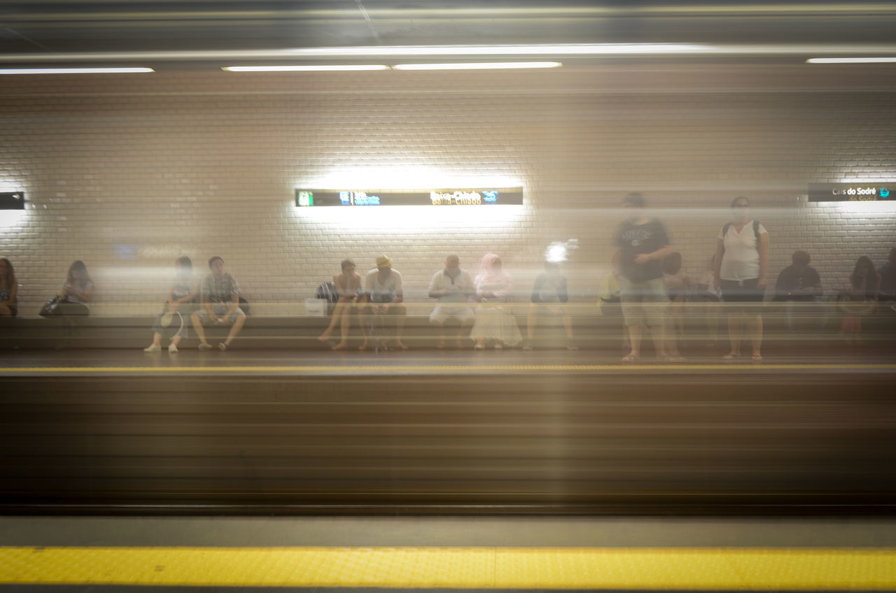 blurred motion, illuminated, indoors, real people, transportation, subway station, public transportation, motion, men, speed, long exposure, large group of people, lifestyles, women, subway train, defocused, people, adult, day, adults only