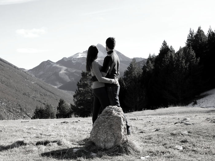 Couple embracing on mountain against sky