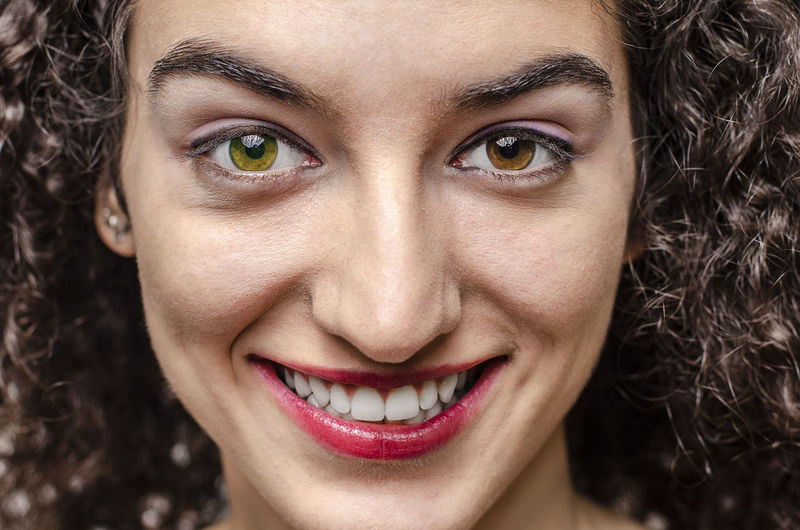 Portrait Young Adult Human Body Part Women Emotion Human Face Beautiful Woman Looking At Camera Smiling Happiness Beauty Close-up Studio Shot Make-up Headshot Human Teeth Human Lips Lipstick Curly Hair Brunette Different Eyes Weird Eyes