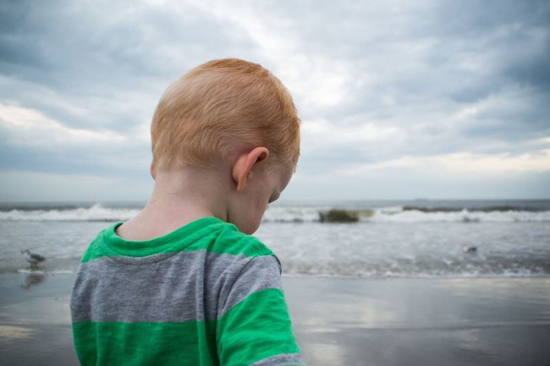Midsection of young boy standing on beach