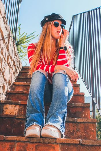 Low Angle View Of Young Woman Sitting On Staircase