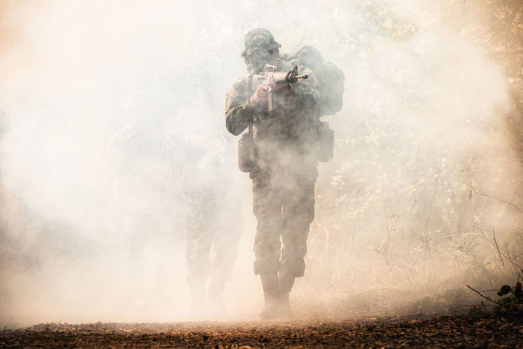 Army soldier shooting with rifle during foggy weather