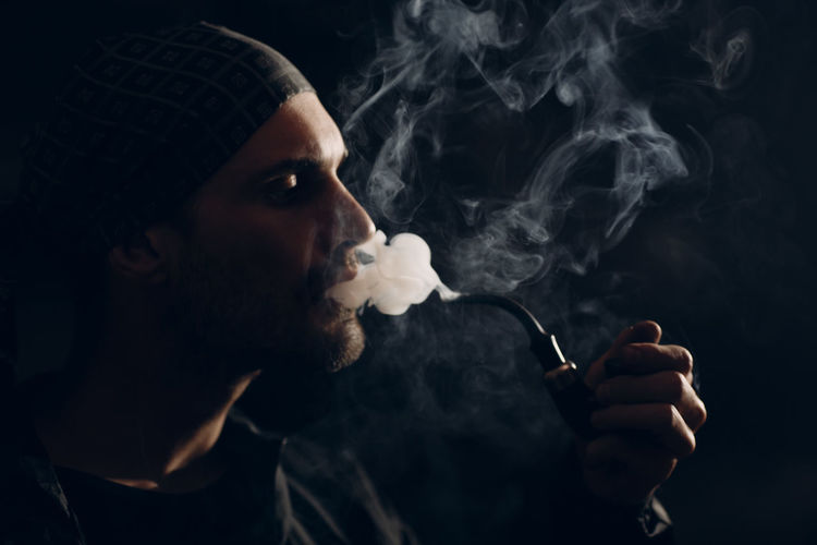 Close-up of man smoking against black background