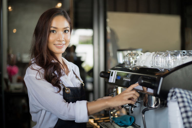Portrait Of Smiling Young Woman Working In Cafe