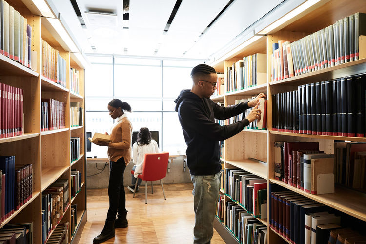 Man and woman standing on shelf in library