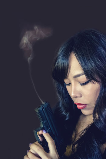 Close-Up Of Woman With Handgun Against Gray Background