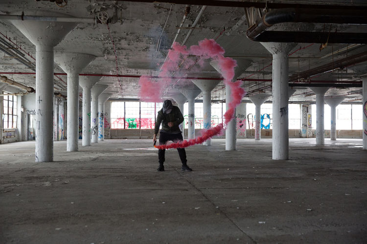 Smoke Grenade Adult Architectural Column Architecture Built Structure Casual Clothing Day Full Length Indoors  Leisure Activity Lifestyles Long Hair One Person People Portrait Real People Standing Young Adult