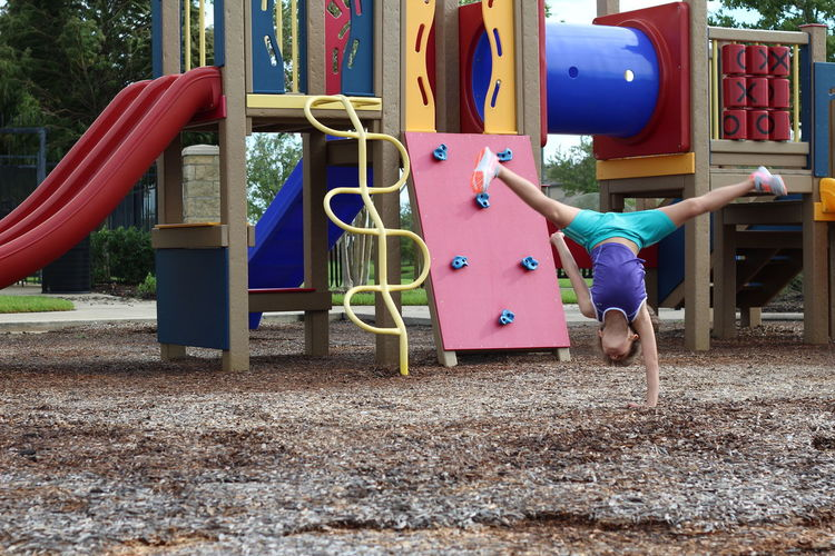 Girl practicing handstand against jungle gym at playground