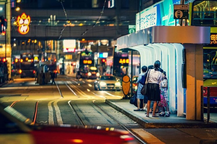 People waiting for tram on street in city at night