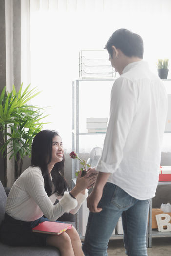 Picture of young man surprising woman with flowers Two People Casual Clothing Young Women Young Adult Women Lifestyles Young Men Togetherness Adult Standing People Sitting Couple - Relationship Valentine's Day  Surprise Love Flirting Dating Birthday ASIA Happiness Relationship Girlfriend Boyfriend Friendship