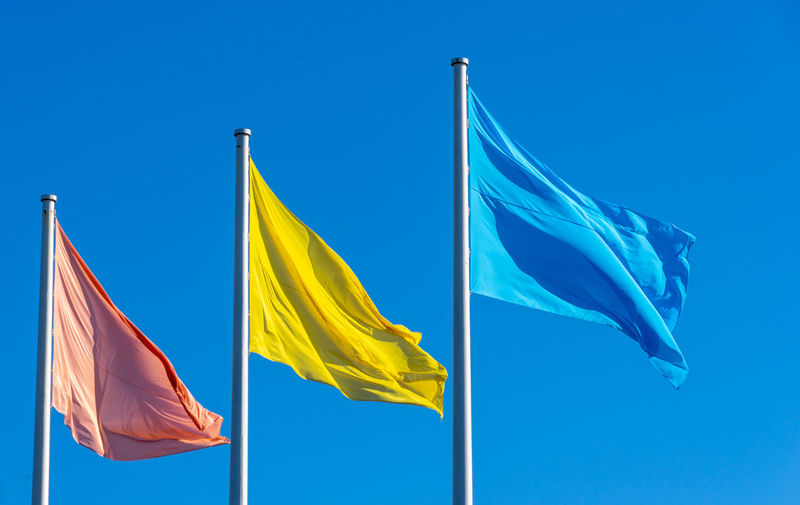 Blue Flag Summer In The City Blue Blue Sky Clear Sky Day Emotion Environment Flag Flags In The Wind  Low Angle View Nature No People Outdoors Patriotism Pole Positive Emotion Pride Red Red Flag Sky Sunshine Textile Waving Wind Yellow Yellow Flag Analogue Sound