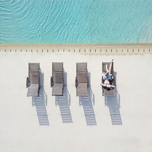 High angle view of man sitting by swimming pool
