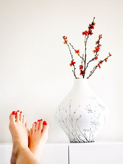 Low Section Of Legs Crossed At Ankle With Vase Against Wall