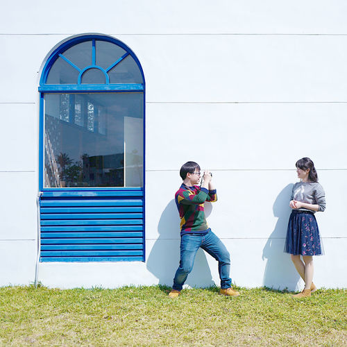 Young man photographing woman using camera against wall