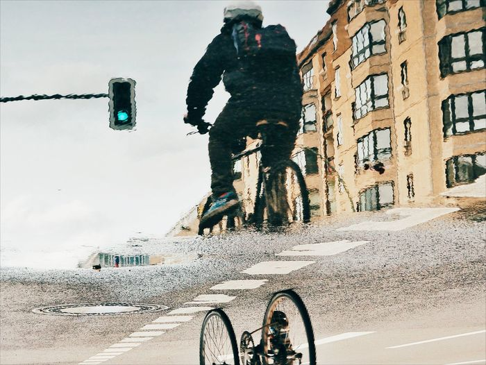 Upside down image of man reflection in puddle while riding bicycle