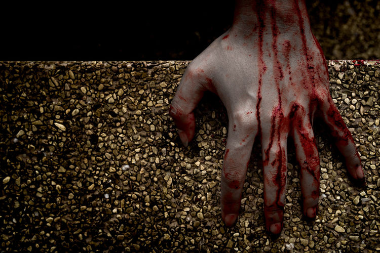 Cropped Image Of Woman Hand Covered With Blood On Floor