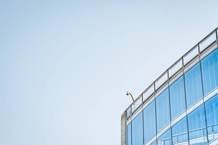 Low angle view of bird perching on building against clear sky