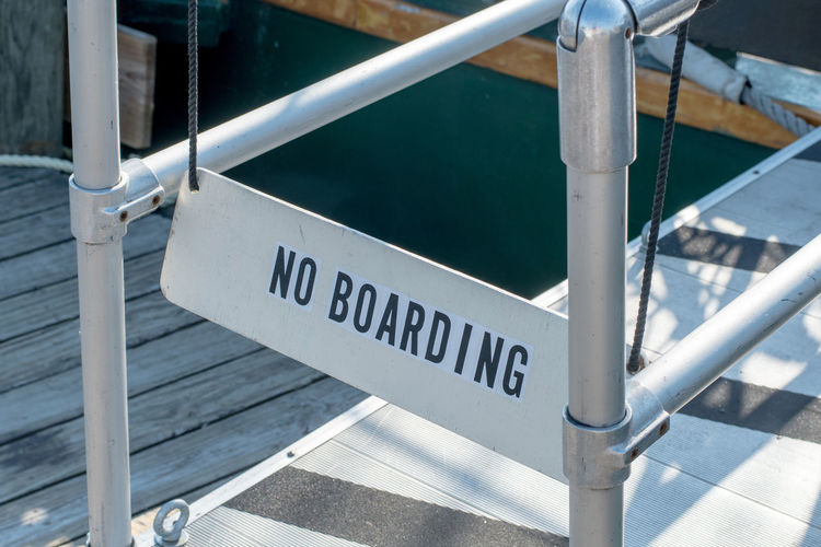 A no boarding sign blocks a gang plank to stop people  from boarding a boat