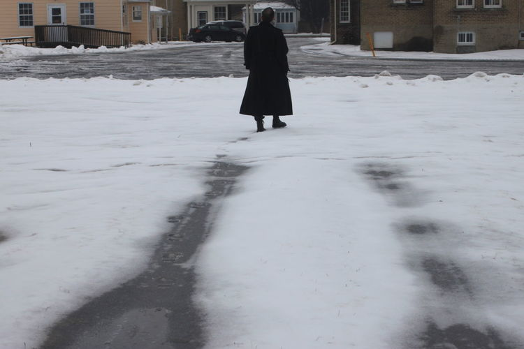 Rear View Of Man Standing On Snow Covered Road