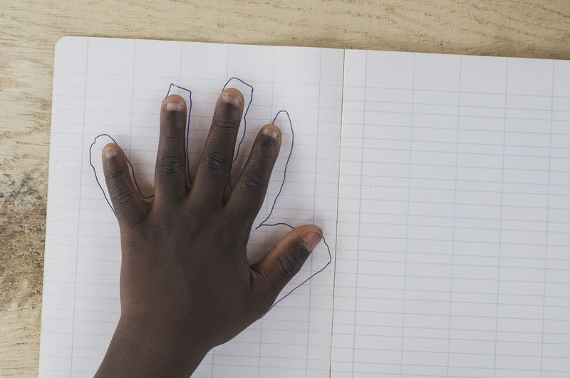 High angle view of human hand against white wall