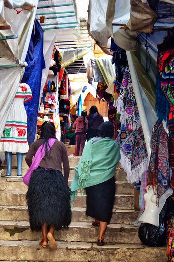 Rear view of people walking on street market