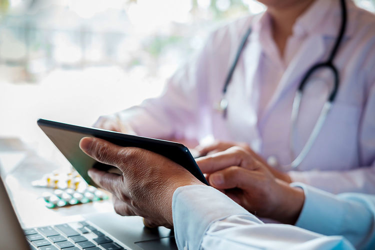 Midsection Of Doctors Discussing Over Digital Tablet
