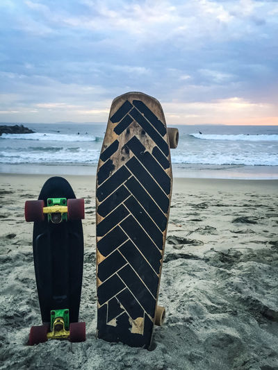 Skateboards On Sand Against Sea During Sunset