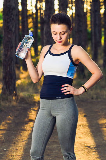 Young Woman Drinking Water While Standing Against Trees In Forest During Sunset