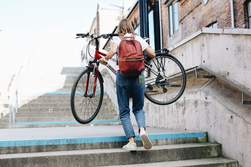 Full length of man standing on bicycle in city
