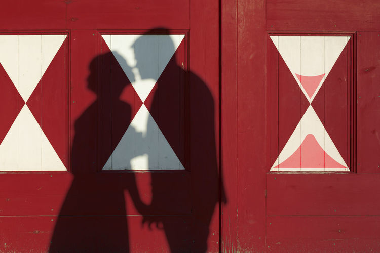 Shadow of kissing couple on red door