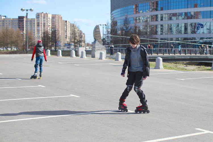 Teenage girl inline skating at parking lot in city