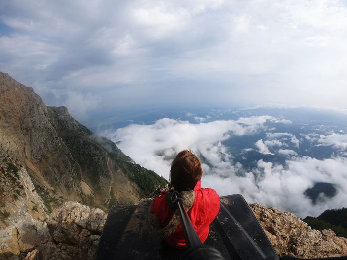 Rear view of woman relaxing on mountain peak against cloudy sky